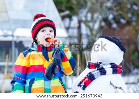 Funny little child making a snowman and eating carrot, playing and having fun with snow, outdoors  on cold day. Active outoors leisure with kids in winter. - stock photo