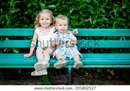 funny little children brother and sister sitting on bench - stock photo