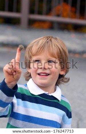 Funny little curious boy with the bur on his finger - stock photo