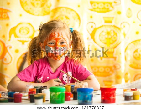 Funny little girl artist with paint of face. - stock photo