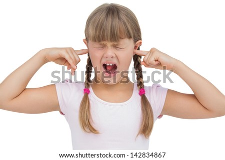 Funny little girl clogging her ears and wincing on white background - stock photo