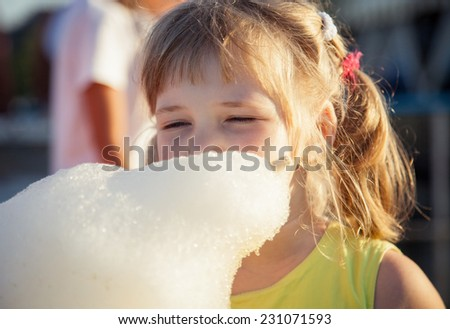Funny little girl eating cotton candy - stock photo