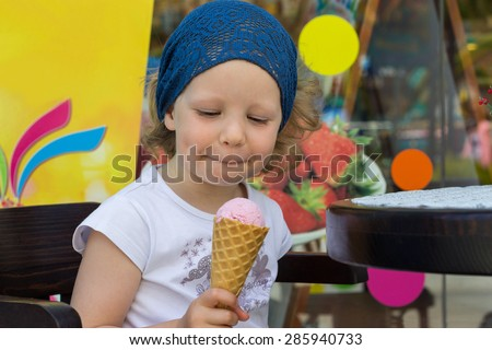 Funny little girl eating ice cream. Selective focus. - stock photo