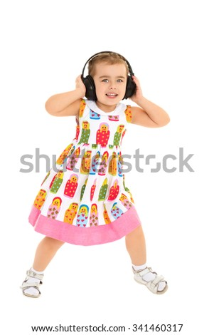 Funny little girl in big black headphones is listening to music and dancing-Isolated on white background - stock photo