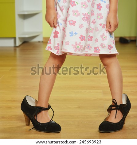 Funny little girl in her mother's big shoes - stock photo