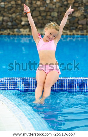 Funny little girl in the swimming pool - stock photo