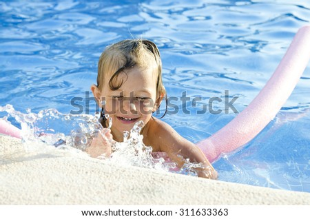Funny little girl learning to swim with pool noodle - stock photo