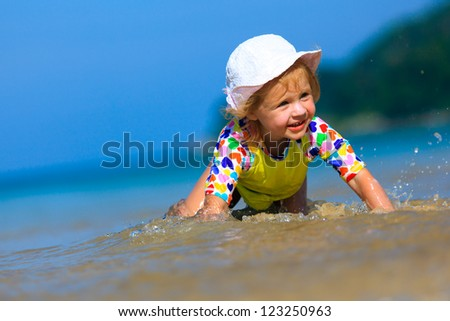 Funny Little girl playing on the beach - stock photo
