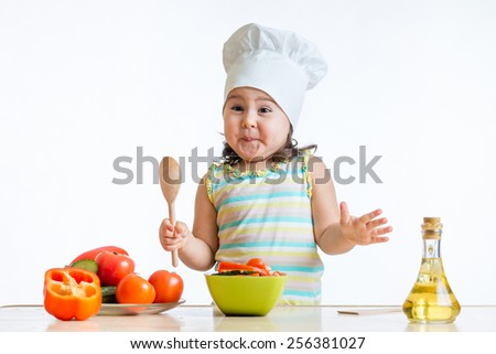 funny little girl preparing vegetables salad isolated - stock photo