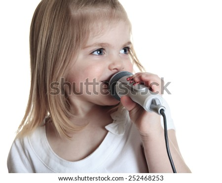 Funny little girl singing with a microphone isolated on white background - stock photo