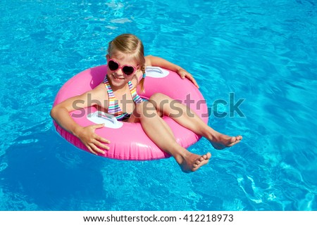 Funny little girl swims in a pool in a pink life preserver - stock photo