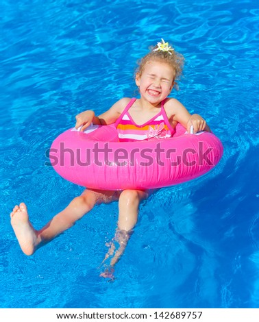 Funny little girl swims in a pool in an pink life preserver - stock photo