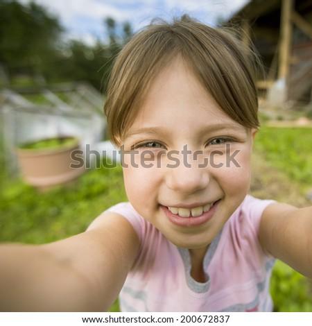 Funny little girl taking self portrait (selfie) outdoors. - stock photo