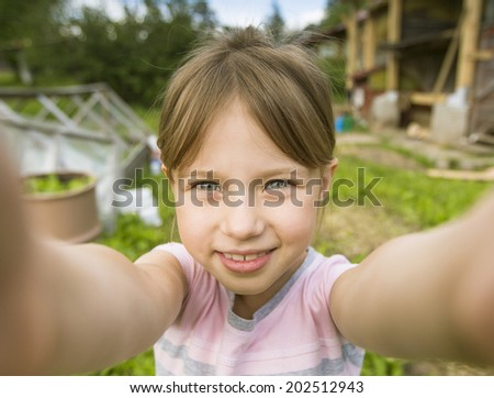 Funny little girl taking selfie outdoors. - stock photo