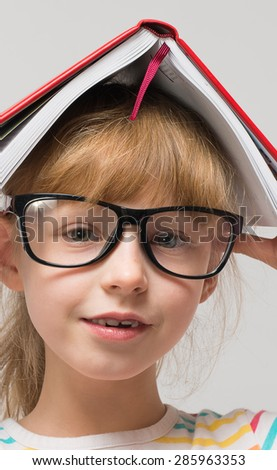 funny little girl with a book  - stock photo