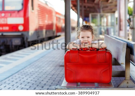 Funny little girl with big red suitcase on a railway station. Kid waiting for train and happy about traveling. - stock photo