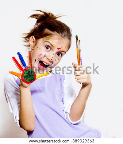 Funny little girl with colored face using watercolours - stock photo