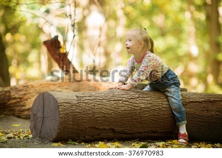 funny little girl with Down syndrome sitting on a large log - stock photo