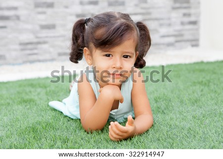 Funny little girl with pigtails lying on the grass - stock photo