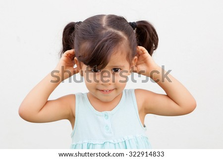 Funny little girl with pigtails making the gesture to hear - stock photo
