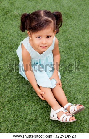 Funny little girl with pigtails sitting on the grass - stock photo