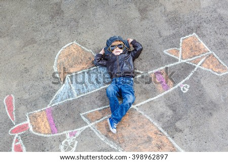 Funny little kid boy flying by a plane picture painting with colorful chalk. Creative leisure for children outdoors in summer. Child playing the little prince figure. - stock photo