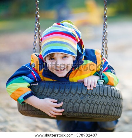 funny little kid boy having fun with chain swing on outdoor playground. child swinging on warm sunny spring or autumn day. Active leisure with kids. Boy wearing colorful clothes - stock photo