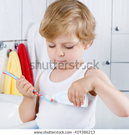Funny little kid boy learning brushing his teeth in domestic bath. Children learning how to stay healthy. - stock photo