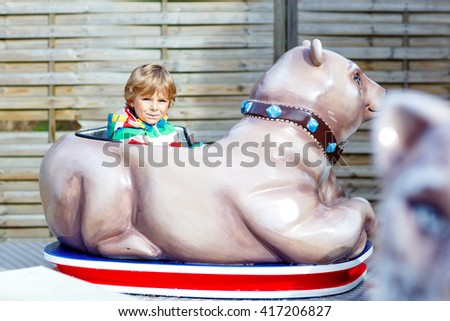Funny little kid boy riding on animal on roundabout carousel in amusement park. Happy preschool child having fun outdoors on sunny day. - stock photo