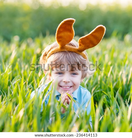Funny little kid boy with Easter bunny ears playing in green grass on sunny spring day, celebrating Easter holiday - stock photo