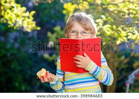 Funny little kid boy with glasses, books, apple and backpack on his first day to school or nursery. Child outdoors on warm sunny day, Back to school concept - stock photo