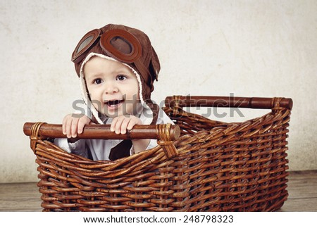 Funny little pilot in wicker basket - stock photo