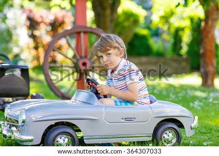 Funny little preschool kid boy driving big toy old vintage car and having fun, outdoors. Active leisure with children during school holidays on warm summer sunny day. - stock photo