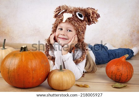 Funny little preschooler with pumpkins - stock photo