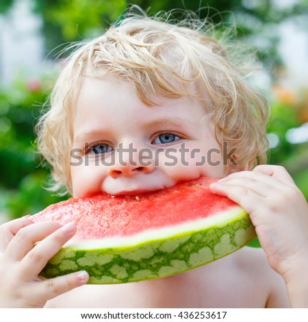 Funny little toddler boy with blond hairs eating watermelon in summer garden. Kid tasting healthy snack. Healthy food for children. - stock photo