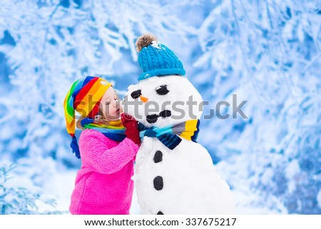 Funny little toddler girl in a colorful hat and warm coat playing with a snow man. Kids play outdoors in winter. Children having fun at Christmas time. Child building snowman at Xmas. - stock photo