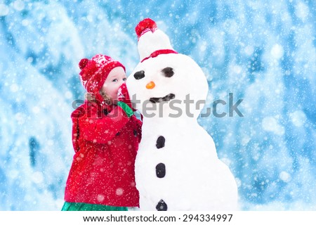 Funny little toddler girl in a red knitted Nordic hat and warm coat playing with a snow. Kids play outdoors in winter. Children having fun at Christmas time. Child building snowman at Xmas. - stock photo