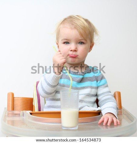 Funny little toddler girl in blue stripes sweater drinking milk from the glass with straw sitting indoors in high feeding chair against white wall - stock photo