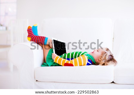 Funny little toddler girl with tablet pc relaxing on a white couch - stock photo