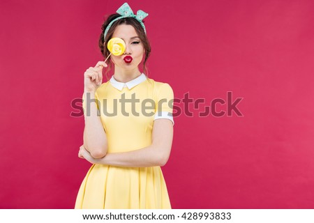 Funny lovely pinup girl covered one eye with yellow lollipop and sending a kiss over pink background - stock photo
