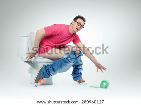 Funny man dropped the toilet paper sitting on the toilet. Situation concept - stock photo