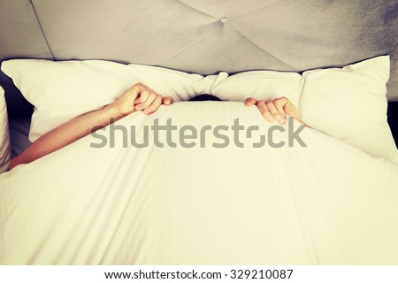 Funny man hiding in bed under the sheets. - stock photo