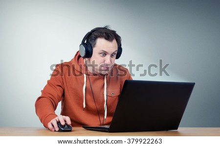 Funny man in headphones with laptop. Game-play - stock photo
