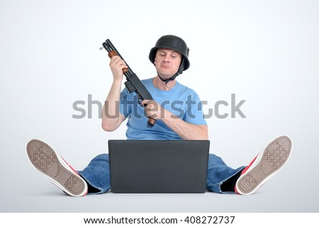 Funny man in helmet with shotgun sitting on the floor front of a laptop. Armchair warriors concept - stock photo