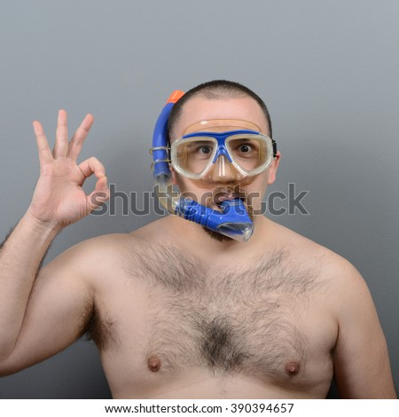 Funny man wearng diving mask against gray background - stock photo