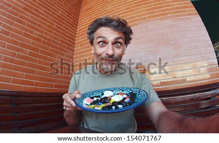 funny man with candy assortment - stock photo