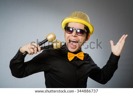 Funny man with mic in karaoke concept - stock photo