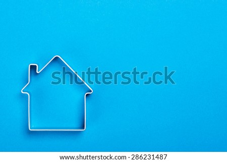 Funny metal house standing on a blue surface - stock photo