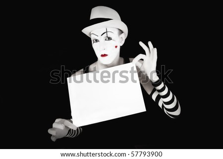 Funny mime in striped gloves and hat, holding a white  blank on a black background - stock photo