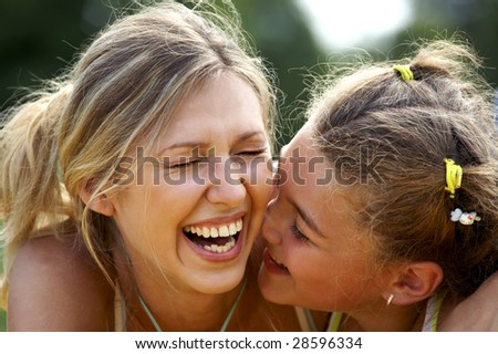 Funny mom and daughter smiling outdoors - stock photo